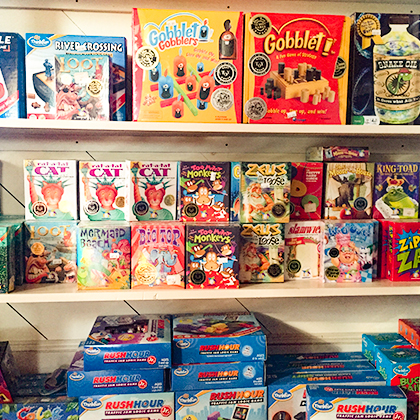 Three shelves filled with a variety of board games.