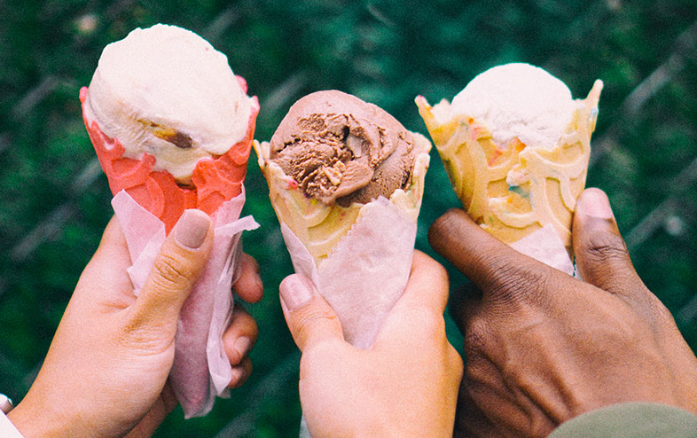 Three people holding a variety of different flavored ice cream in cones.